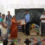 Gandhigram - Glovis staff present materials to school teacher.